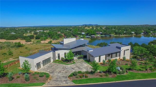 Designed by Dick Clark! This Hill Country contemporary estate includes 4 bedrooms, 4 baths, 2 half baths, a study, and wine room. Everything about this home is first class, from the state of the art appliances and custom cabinets to the exquisite finishes. The 1.75 acre waterfront lot offers panoramic views of Lake LBJ and Packsaddle Mtn that can be enjoyed from your expansive deck or infinity edge pool and hot tub. Soak in lakeside living with 341ft of waterfront, including a boat dock w/ electric lift.