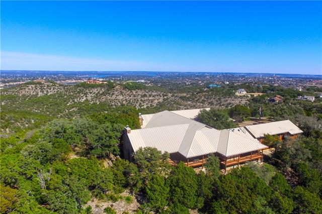 Extraordinary 85 acre, gated estate in the heart of Lakeway. Incredible views from one of the highest hills in the area. Total privacy from this nearly 11,000 sq ft Colorado style Mountain Lodge plus approx 2500 sq ft of outdoor living areas. 2bed/2bath guest cottage. Not in city limits, no restrictions! This would make an incredible venue or development opportunity with water/sewer. Frontage on Serene Hills & Flint Rock Rd. Lake Travis ISD!