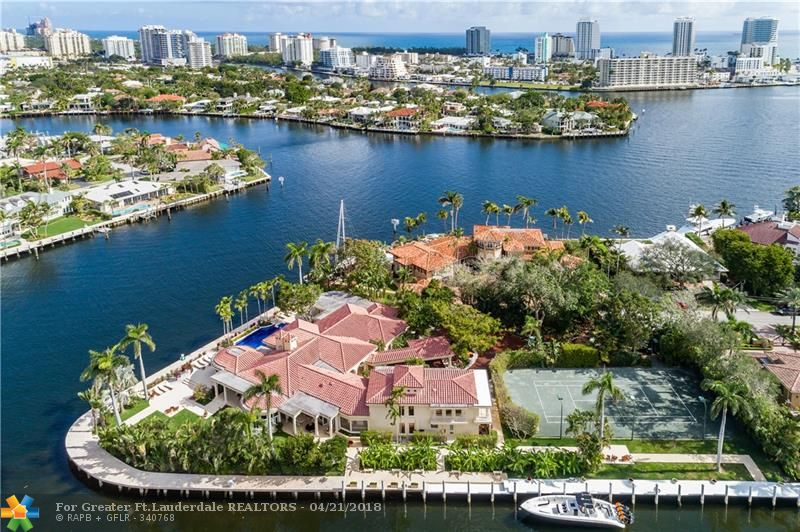 Secluded estate on a spectacular & very large (over an acre) point lot with tennis court. Just moments from the Intracoastal with 550' of deep water frontage on wide canal, can accommodate a vessel in excess of 200'. This unique property is very private & completely gated w/welcoming porte cochere. Ground floor master suite. Fabulous, private & covered outdoor entertaining & dining areas. Located in the tranquil Seven Isles Community off of Las Olas, community security office and optional security patrol.