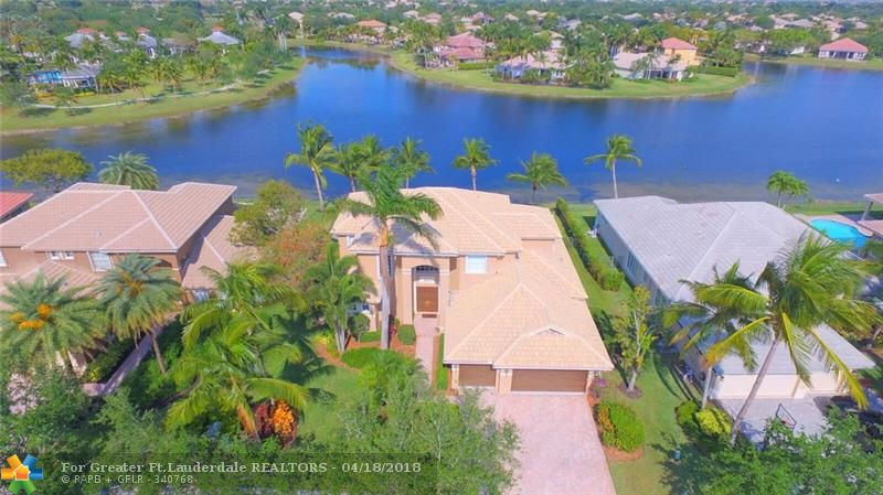 Gorgeous waterfront home with amazing water views in the Estates section of Parkland Isles! This fantastic 5 bedroom, 4 bath home is situated on one of a few waterfront point lots! Fabulous kitchen with Granite, center island and stainless steel appliances including double oven. Large Master bedroom with 2 walk-in closets and large master bath. Second bedroom on the first floor and dual staircases. Screened covered patio, large pool and lush landscaping with beautiful palm trees.