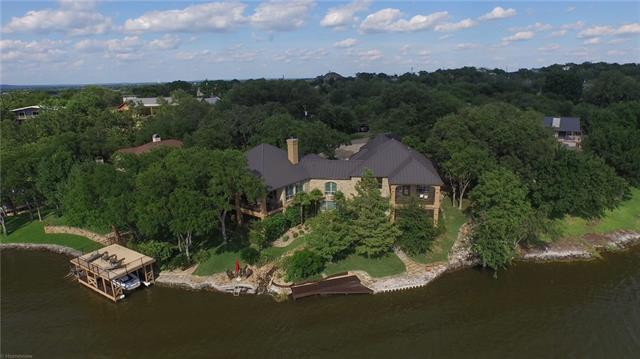"Appx 6,000 sf Lake LBJ waterfront home, 206' big, deep open water. Extensive remodel in 2014. Granite, stainless, hickory, travertine, & slate floors, alder cabinets, 6 refrigerators, 6 HD flat screen TVs. Gourmet kitchen, 5 bedrooms, 5 ½ baths, 2 dining, living, game & media rooms w/ 3D HD 100""screen, casita, outdoor kitchen. 1,500+ sf of patios under roof w/ slate floors. Waterfall feature. Boat dock w/ lift, 2 jet ski ramps.  Priced furnished, few exceptions. Owner is Texas licensed real estate agent."