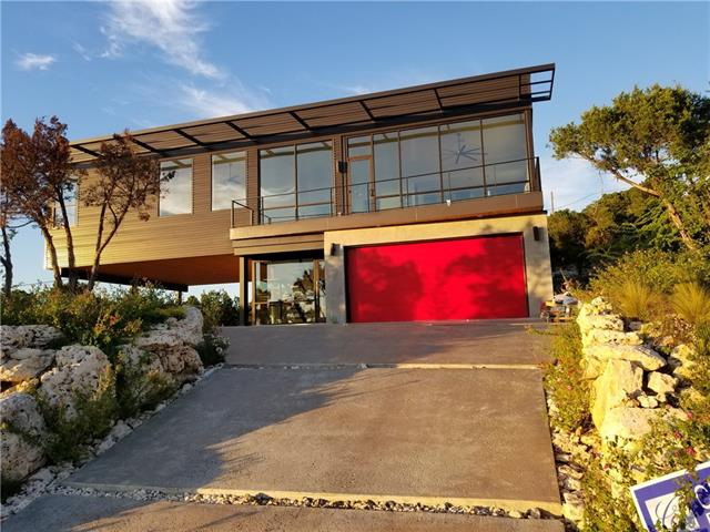 """AMAZING MODERN/INDUSTRIAL home with PANORAMIC VIEW (LAKE TRAVIS). Over 1000 SF Covered Patio/Decks. WALLS OF GLASS. Tongue-in-Groove wood ceiling over patio. Steel I-Beams, Concrete, and Glass exterior finishes. FLOATING STEEL STAIRCASE. STAINLESS STEEL CABLE RAILING. 12' Ceilings. WIDE PLANK European White Oak Floors. Outdoor Fire Pit. Walk-in showers with 20"""" rain head. XERISCAPED landscape."""