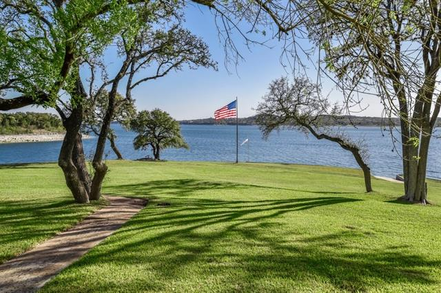 Modern traditional home on a beautiful stretch of 200' of Lake Travis waterfront. Home is luxurious and relaxed with fine finishes throughout. Main living with high peaked ceilings and panoramic windows. Private study, exercise/flex room, wine storage and beautiful stone patios with spa, bar and grill. Home caters from exceptional living and entertaining and enjoys amazing outdoor access with private yard and lake access with boat ramp. Optional additional purchase of adj' tract MLS#9306402