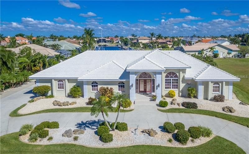 """PGI!  CUSTOM 3/2/3 FERO-BUILT SAILBOAT ACCESS POOL HOME WITHIN MINUTES TO CHARLOTTE HARBOR! GORGEOUS LONG WATER VIEWS!  Simply stunning inside and out.  Impeccable landscaping, tiled front entrance, double front door with leaded inserts, vaulted ceilings and 18"""" diagonal tile. Kitchen features glazed maple cabinets with pan drawers and pull outs, granite, tile backsplash, stainless appliances, Pegasus sink, crown molding with custom lighting, tray ceiling, closet pantry, butler pantry and breakfast bar.  Breakfast room includes 3 store front tinted windows to enjoy the water views.  Formal dining room and living room offering slider access to lanai.  Spacious master suite with walk-in closet, separate lanai area to pool and private ensuite featuring dual vanities with tower cabinets, granite, spa tub, and walk-in glass block shower.  Two guest bedrooms with large closets and guest bath with maple cabinetry, granite and Travertine marble shower which is accessible to lanai and large interior laundry with plenty of cabinets. Covered outdoor lanai features 1,000 sq. ft. of entertaining area with stamped concrete, stylish wet bar and 28' x 14' screened heated pool and spa. 3 car air conditioned side-load garage with craft room and extra large driveway for parking. 65 feet of water frontage, concrete seawall, 10,000 lb boat lift, and dock with electric and water just waiting for your boat. Close to I-75, restaurants, Yacht Club, Fishermen's Village, and the historic district of Punta Gorda. CALL TODAY! <Red><Big><B> For Free Recorded Info 24/7 Call 1-800-327-6040 Ext 588 </Red></B></Big>"""