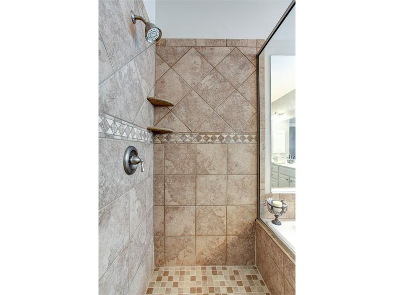 This shower has been done to match the flooring and tub casing creating a very custom feel.
