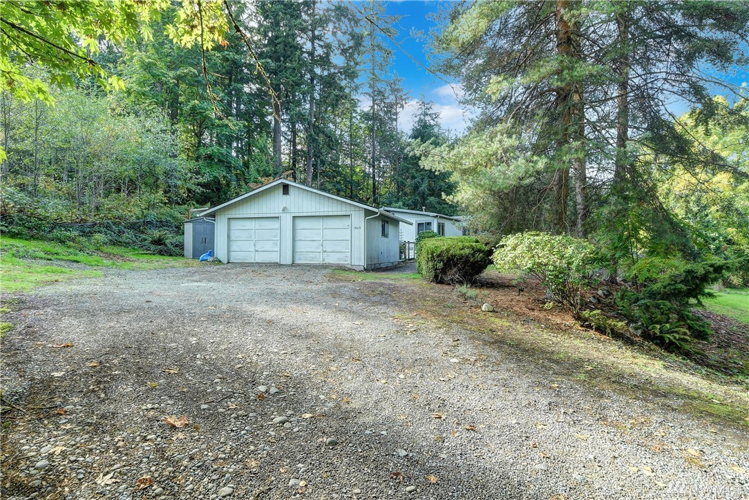 Secluded city oasis. Large, wooded 1 story Rambler w/detached 2-car garage & shop.  Built on poured concrete foundation. This DW MHome offers 3Bd (1 with a walk-in closet) & 2Bth. Well equipped kitchen, dining room, living room & plenty of storage. Vaulted ceilings, skylights & ceiling fan. Plus bonus recreation room. Outdoors has gardening space, deck, built-in cascading pond, blackberry bushes & lots of wildlife. Centrally located to mountains & waterfront. Aerial video: https://bit.ly/2QTFAaU