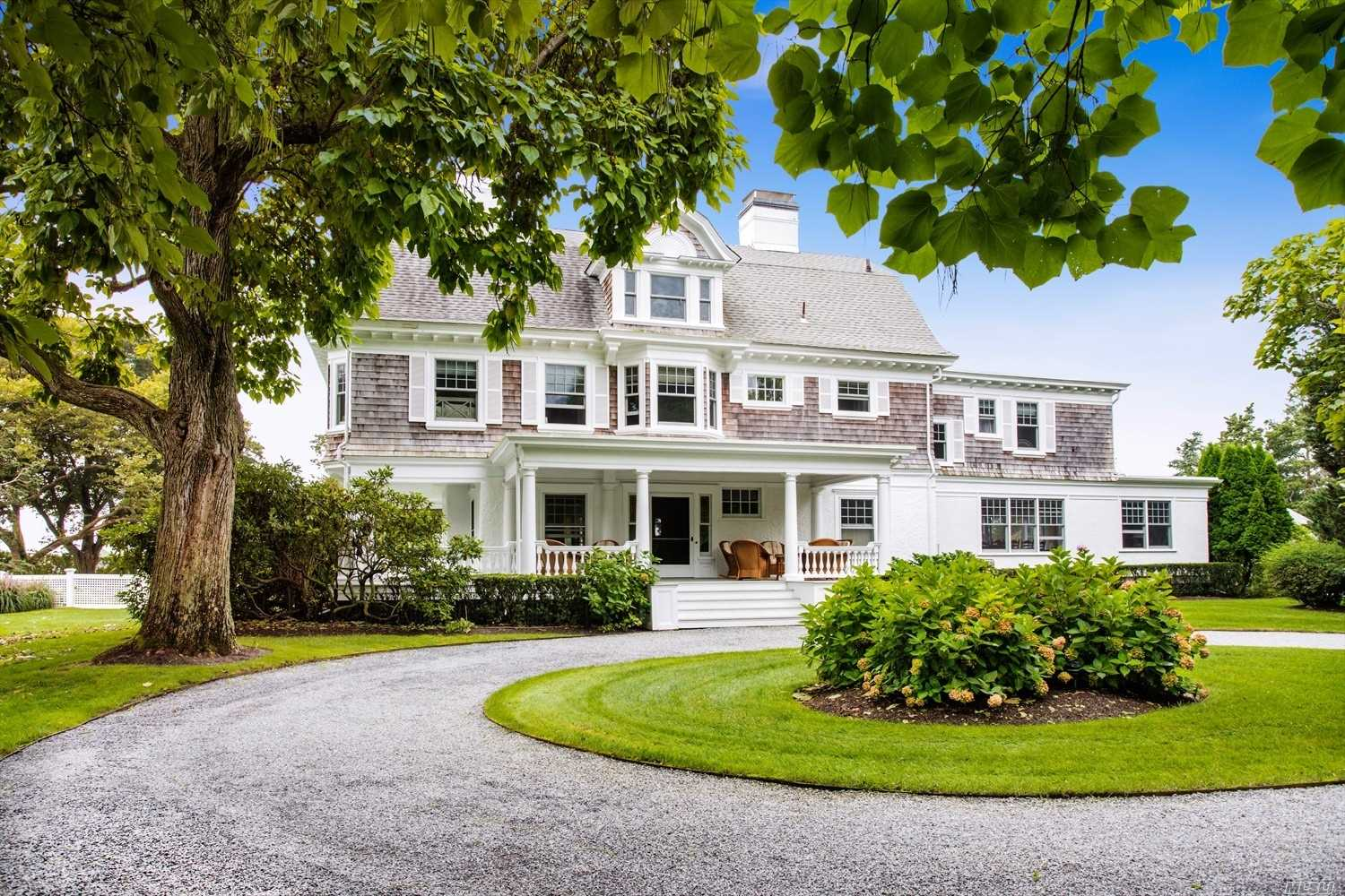 Set On Two Manicured Acres In The Heart Of Quogue's Most Prestigious Estate Area, This Stately Shingle-Style Colonial Revival Is A Glorious, Pristine Example Of The Golden Age Of The Early 20th Century On The East End Of Long Island. Historic Trees Shade The Approach To The Over-Sized Entry Door That Is The Centerpiece Of The Wide, Hipped-Roof, Wrap-Around Porch. Inside The Home, A Double Living Room With Gleaming Century-Old Floors, And The Original 1903 Patterned Tin Ceiling Greet The Visitor.