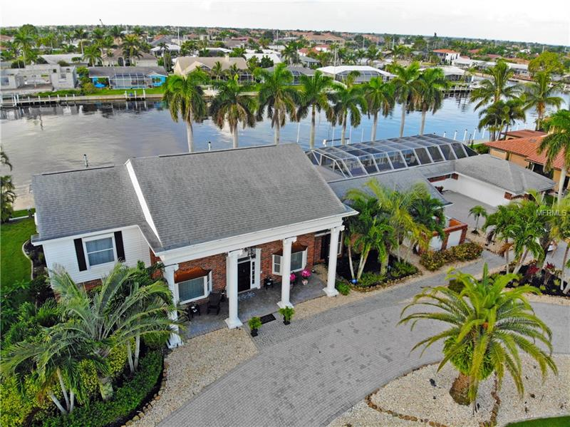 Captain's Paradise in beautiful Punta Gorda Isles is just 500ft from the Charlotte Harbor. With 180' of seawall, 90' dock, and a 12k lb lift in the backyard, this location is ideal for your 35' power boat alongside your luxurious yacht or sailboat. This custom built 2 story Plantation Style Home was constructed in 1971 on a double lot of over ½ an acre, has withstood hurricanes Charley & Irma with NO DAMAGE. The circular driveway made up of charcoal cobble pavers leads you to the beautiful acorn pediment accented front entrance. Take a step into the home to be greeted by a dual sided Coral fireplace embracing relics of Key West's Coral Reef. Make way into the Dining room or Billiard room to accompany your greatest friends with a beverage from the wet bar or mouthwatering meal from the newly remodeled waterfront facing kitchen with stainless steel KitchenAid appliances. The great room opens to the lanai through sliding glass doors complimented  as well as the recently renovated Master Suite wiht built-in gas fireplace & flat screen TV, bamboo floors, and walk-in Closet. The staircase leads you to 2 guest bedrooms and an additional master suite with walk-in closet. Enjoy a meal prepared from your summer kitchen just a few feet from the cascading waterfalls of natural rock heated spa & swimming pool. Exiting the lanai is the secondary driveway surrounded by two garages with space for 4 cars, a workshop, a fishing closet, and room for your favorite toys. Set an apt to make this unique luxury home yours today!