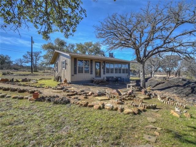 """Step back in time in this story-book cottage, reminiscent of """"Little House on the Prairie""""! A true artist's retreat, this spellbinding property is aptly named """"Star Light, Star Bright"""". Wood floors, high ceilings, river-rock hand-laid fireplace, open floor plan, towering oaks, wet-weather creek & large granite outcroppings are some of the many features of this unique get-away. Furn. & furnishings available by sep. bill of sale. Enjoy community parks, boat ramp, picnic areas and day dock!"""