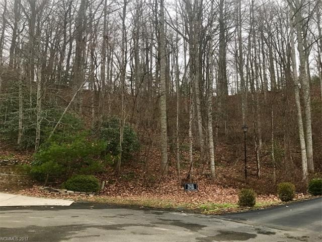This exquisite mountain homesite is nestled among the trees, overlooking astounding mountain views and tucked in Fairview & the Cane Creek Valley. This homesite is perfectly suited for a daylight/walk-out basement style construction with the privacy of a cul-de-sac lot.  (View Photo from adjacent porch.)