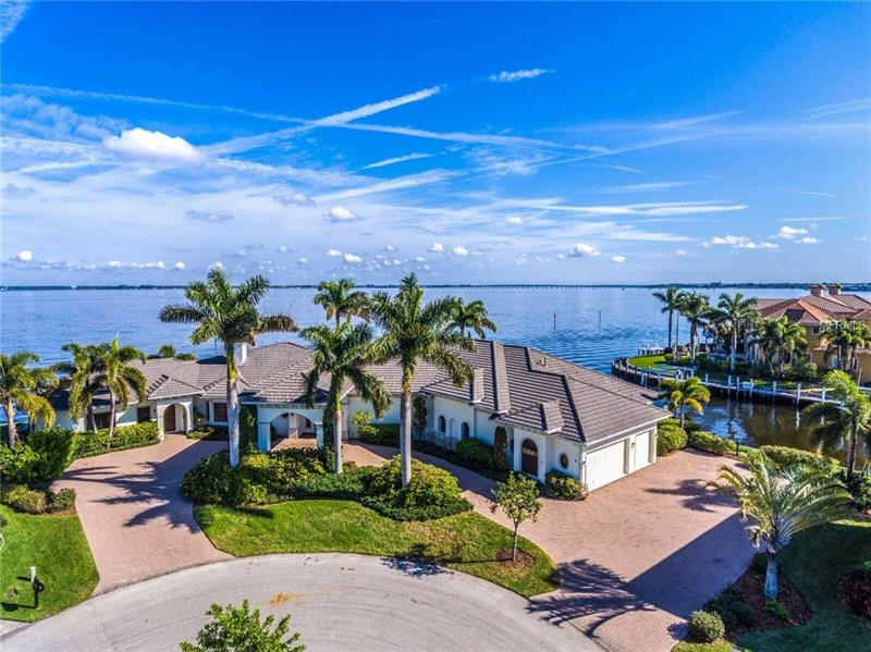 RARE OPPORTUNITY to own PRIME HARBOR FRONT location with 390 ft of waterfront! Custom-built in 2007 by award-winning SandStar /Rutenberg Homes, this home is elegant yet designed for casual living and fabulous entertaining. Impressive architecture starts with the porte-cochere where you enter the beautifully arched front door opening to the grand foyer and a panoramic view of Charlotte Harbor. No need to choose between sunrise and sunset, you can enjoy both from the 2,133 ft wrap-around lanai. Truly a chef's kitchen with handsome  granite gracing the counters, featuring center island, beverage island and buffet island.  High-end appliances include Sub-Zero refrigerator, Wolf 6-burner gas stove with pot filler, dual dishwashers and ovens. Excellent 'flow' takes advantage of the stunning view from the kitchen to an expansive dining room and on to the living room featuring coffered ceilings, fireplace and zero-corner sliding doors to the outdoor living space. The luxurious master suite includes an en suite bath with his/hers vanities and water closets, bidet, and dressing room with built-in shelving. The west wing offers a separate entrance to a two-room suite with Jack & Jill bath and the fourth bedroom with a private bath. High ceilings, heated infinity-edge pool, impact windows & doors, storm protection for lanai, 3-zoned A/C, so much more, please see supplement.  Situated on a tip lot + 2/3 of the key lot for a total of .62 acres. Spectacular views of 4th of July fireworks, boat races, birds & dolphins!