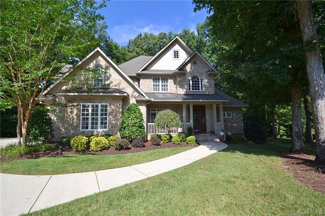 This custom full-brick home in Ellington Farm sits on a wooded, fenced lot that backs to trees. The backyard lanai has a brick fireplace, a built-in stainless steel grill and a stamped concrete patio. This home has an attractive elevation with a covered front porch sheltering the mahogany front door with glass panels. The open floor plan has site-finished hardwood floors on the main level and extensive moldings throughout.  The master suite and a guest bedroom are both on the main level. The cook's kitchen features granite counter tops, stainless steel appliances and is open to the great room. The great room features a stacked stone fireplace and plenty of room for furniture. The updated master bathroom has subway tile flooring, granite vanity, a frameless glass shower with a rain head fixture, and a large walk-in closet with built-ins. Enjoy time with family and friends in the oversized bonus room upstairs.  The crawlspace is sealed with a humidifier.