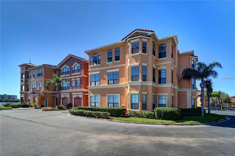 """LOCATION, LOCATION, LOCATION with spectacular unobstructed waterviews of """"Old Tampa Bay"""" in the gated waterfront community of The Grand Bellagio at Baywatch!  This second floor Toscano model is very private; located at the end of the community in Bldg 13 on the open water and having numerous windows that wrap-around the entire corner condominium unit to capture the serenity and beauty of nature.  A two bedroom two bath split bedroom plan with wood kitchen cabinetry, granite countertops, kitchen eat-in area, closet pantry and breakfast bar.  Bay window in dining, gas fireplace in living room with ceramic tile through the entire living/dining/hallway/utility rm areas; granite bath vanities with tile bath floors; updated master bedroom bath shower; crown molding, upgraded stainless steel refrigerator and dishwasher; newer hot water heater.  Condominium comes with single car garage G-133 located underneath the building with side pedestrian door access to the corridor and up the stairs to the condominium.  Gated waterfront community with 24-hr fully equipped fitness center, geo-thermal heated pool and spa; poolside cabanas and screened enclosed cafe area for refreshments; lighted 1.5 mile promenade, car care center with wash and vacuum.  Marina is a separate condominium association for boat slip owners of Grand Bellagio condominiums."""