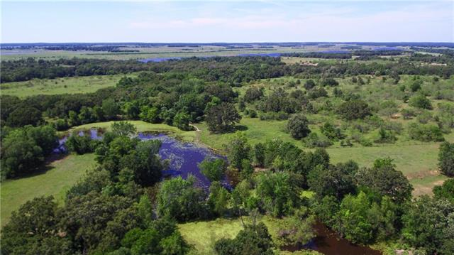 Right on the Lee/Milam county line, this listing has; 89+/- beautiful rolling acres with improved pastures,  large old-growth native oaks, cross fencing, multiple ponds, barn/shed/equipment shed, pipe cattle pens in excellent condition, concrete silage bunker, private water well and road frontage on Hwy. 77 and CR 313. There's an older (1963) custom 2,047 sqft 3/3 brick home with attached garage, vaulted ceilings and den/family room. The home is in livable/rentable condition, but in need of updating.