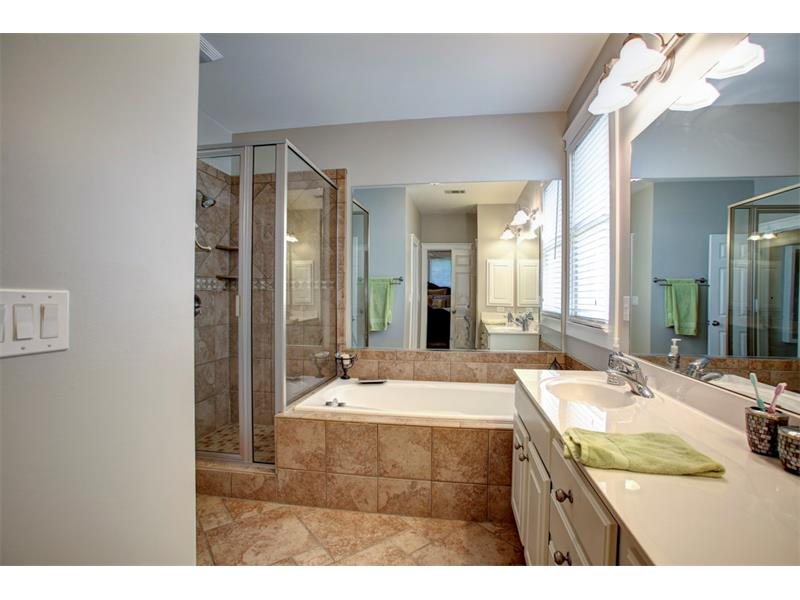 The master bath includes a separate toilet room, large walk-in closet, huge jetted tub and tiled shower.