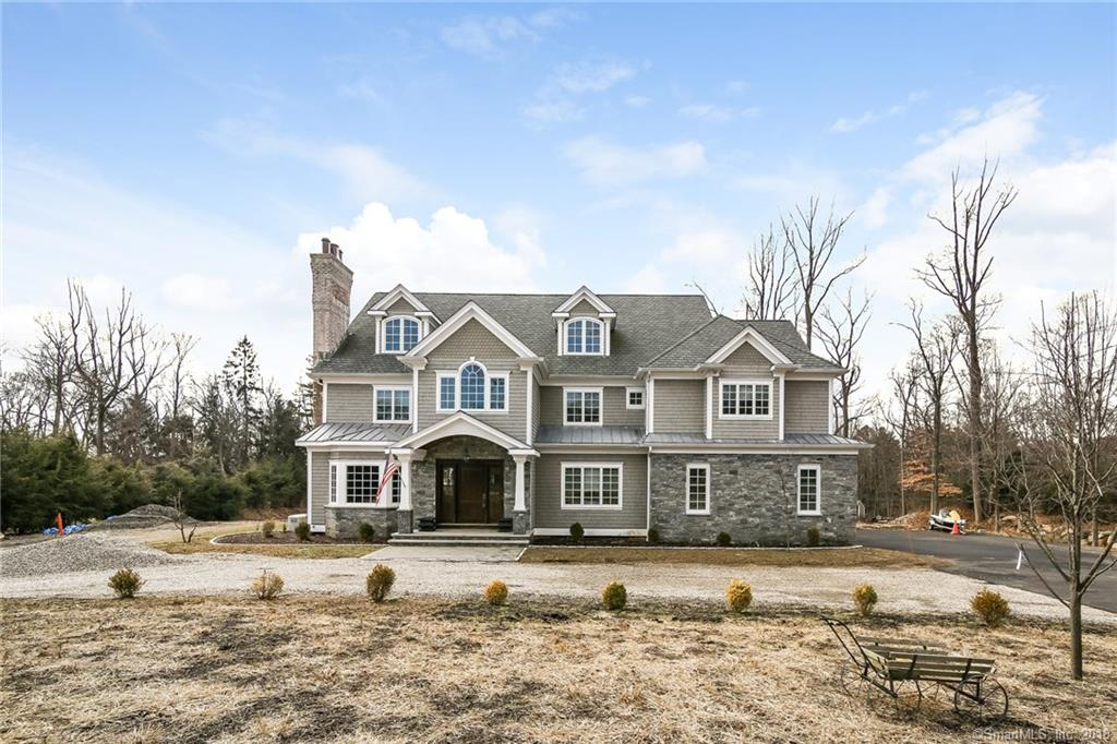"""This stately colonial home was completed in 2017. It is located on 1.69 acres backing up to Dolce and wooded trails. Enter via the crushed stone circular drive and you will find a dramatic two story foyer, herringbone wood designed flooring with an inlaid medallion. There are pocket french doors, a bay window and an incredibly beautiful coffered ceiling in the living room. Another outstanding feature of this lovely room is the herringbone brick work on the inner walls of the fireplace. The formal dining room is very inviting with with raised panel walls and a wonderful recessed center circular ceiling providing dramatic invisible lighting! Many other walls are also adorned with the raised half wall paneling. The bold moldings throughout the house best describe the dynamic affect they bring to each room. The custom designed cabinets are """"perfect"""" as well as the oversized white quartz center island and counter tops with casually placed light lines of grey throughout. All GE Monogram appliances plus a full sized refrigerator, full sized freezer and a breakfast room. Off the breakfast room and into the """"great"""" great room, there is a magnificent stone fireplace with storage for logs, vaulted ceilings, skylight, beams, and plenty of room for a game of pool, TV, games, hobbies or step outside on the deck for some outside fun! There are five bedrooms each with full baths plus two half baths. There is a mud room with full bath and a home office with bath.  See additional remarks:"""