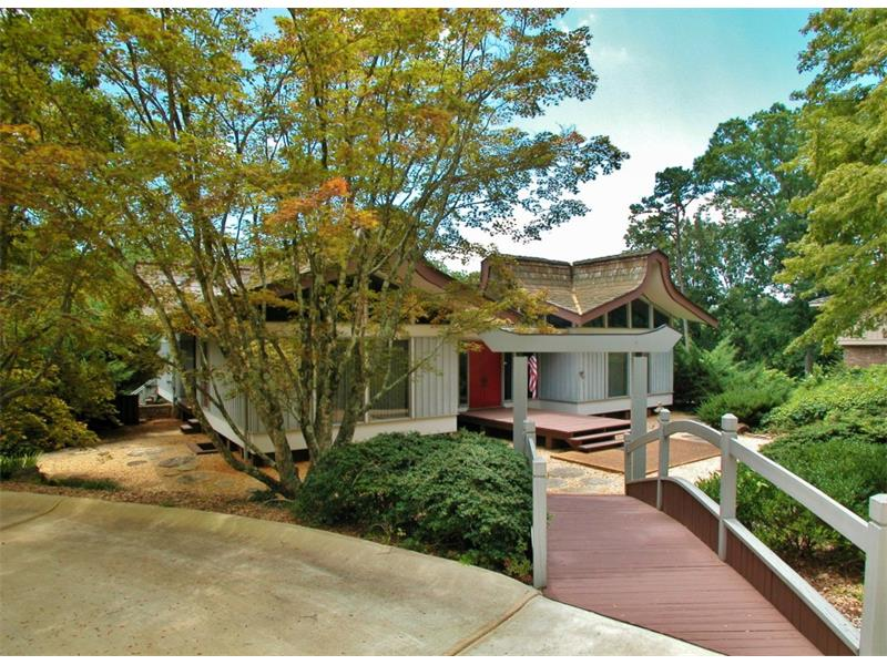 Endless potential with this Lake Lanier home. One of a kind, spacious home situated on 3+ beautiful acres! Gardens and unique architecture make this home a standout! Master on main, 2 fireplaces, large living spaces, storage galore! Bring your vision!