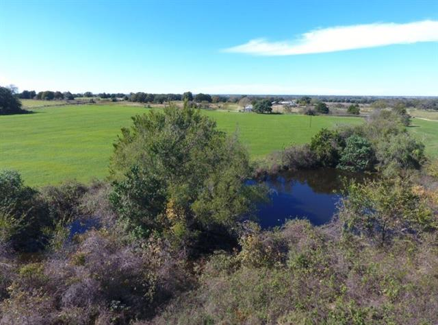 Great place for farm and ranch, recreational, or to build a home.  Fifteen nicely maintained, usable acres of improved coastal, with scattered trees and a pond. Additional 18.74 acres is available for sale. Excellent location with ag exemption in place.