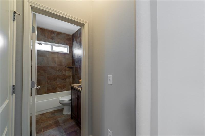 Full bath on main accented by stunning by gorgeous tile, granite countertops & stunning fixtures!