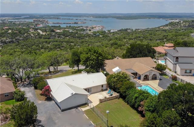 The endless views of the hill country and gorgeous Lake LBJ will draw you to this property! Open floor plan with a large living and dining room, kitchen features large island with a prep sink and mini fridge. A sun-room sits off the living room which can also be accessed from the master bedroom. The master bedroom is large and includes a fireplace and a master bath with a beautiful copper sink. The split bedroom plan. A large back patio with a smaller enclosed patio to enjoy. Extensive guest parking!