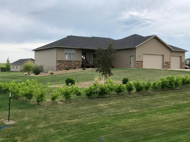This is a beautiful, custom, ranch style home on 1.5+ acres just NE of Bismarck. As you walk in you will see the living room (9' ceilings) with rocked fire place and quarter sawn mantle, handscraped walnut flooring, a large kitchen with gas stove, sit up counter, custom oak cabinets with soft close hinges and touch faucet. There is a maintenance free double deck off the dining area wired for hot tub & piped for natural gas. The laundry & 1/2 bath are entered off the garage. The master en suite has a walk in closet, tiled shower, dual vanities & garden soaker tub. The lower level contains the family room with fireplace & wet bar, 2 bedrooms, full bath, bonus room & large storage areas. The huge garage has H/C water with sink, floor drain, insulated & heated. The 1400 sq. ft. shop is heated, wired for 220 and has attic storage with a ladder & lift. A radon mitigation system is in place. Underground dog fence. Zoned heating. Heated dog house & kennel. Concrete landscape curbing.