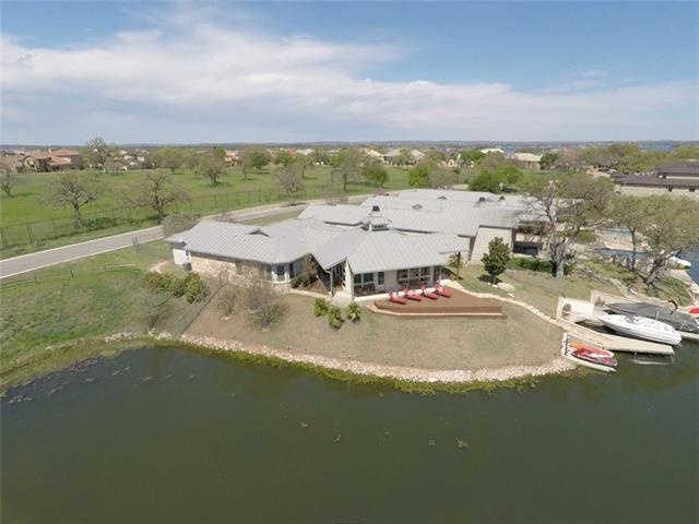 Modern Architectural Masterpiece on Controlled Level Lake LBJ in Horseshoe Bay Resort. Luxury living on 144 feet of a small cove just minutes from open water. Gated complex of only 4 homes in gorgeous Horseshoe Bay West. Private boat slip with hydraulic lift and two personal watercraft ramps. Picture yourself living the lake life in high style and comfort with gorgeous views from the massive great room. Soaring ceilings with a centered fireplace to cozy up.