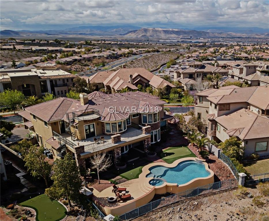 Gorgeous luxury estate, backs up to Rio Secco Golf Course's 8th green, spectacular Strip, golf, city & mtn views! 1/2 acre oversized, fountain, stacked stone, gated covered courtyard, finely manicured lawn, putting green, firepit, refreshing poos, spa, waterfall. Grand entry w/dbl iron & glass door, vaulted ceiling, marble flooring. Custom iron railing, walls of windows, gorgeous casings & molding, softly arched doorways, wood shutters, blinds,