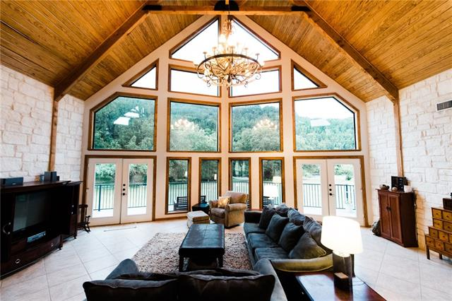 Surround yourself in the BEAUTY of the hill country, yet minutes from shopping, dining, Cedar Park Center & much more. Unique 4/3.5 custom home on 7+ acr near Travisso. Features massive open living spaces w/over 25' ceilings supported by 100' beams and a 2 story fireplace. Floor to ceiling windows that take in sweeping views of creek, hills, and peaceful Valley. Great for entertaining! Property features large ponds, swimming creek, nature and wildlife all around. Bring the horses. Must see to appreciate!