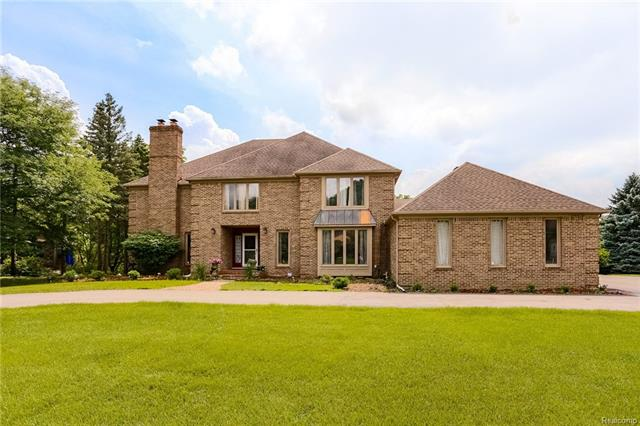 This Farmington Hills Colonial has an entertainer's dream layout. The grand entrance features curved staircases and uniquely beautiful architecture, allowing views into the basement and 2nd floor. The kitchen and huge breakfast nook are open, great for parties. The extra wide butler's pantry makes formal dinners a breeze. Four fireplaces add to the luxurious feel of the property. 1st floor laundry adds convenience, and the laundry room can be used as a 2nd kitchen if needed. The massive master suite has an open bath with soaker tub and enclosed shower, and his/her walk-in closets. A private bath in the princess suite and shared bath in the other two upstairs bedrooms means easier mornings. The large finished basement offers plenty of space for recreation/entertainment, and the 5th bedroom has a private bath and seclusion from the rest of the living space. Backing to woods and minutes from shopping and restaurants, this home's location is excellent. Welcome Home.