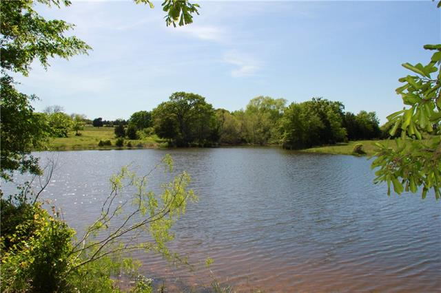 Just 45 min. from Austin, this property is 34+/- acres of beautiful land with lots of scattered trees, a large pond stocked with fish and a nearby bridge over a gulley that leads to a picnic area. It's cross fenced and ready for cattle or horses with a 1500+ sqft 8 stall barn already on the property. The property also has an older, 3/2 double-wide mobile home in nice condition, storage container and a workshop Move in ready, a great weekend retreat or the perfect place to build your dream home.