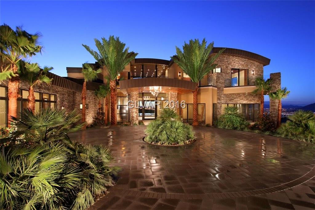 High desert contemporary estate, one of only 9 homes in a neighborhood hidden behind secondary gates. Stunning negative edge pool, spa, waterfall, fire features, floating staircase, elevator, theatre, exercise room, study, two master suites, multiple disappearing walls with full strip views. Neutral tones of walnut/travertine/wallpaper. Designed and built by Sun West Custom Homes.