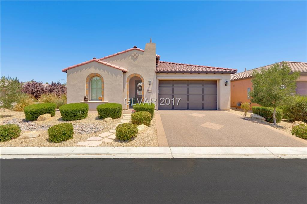 Beautiful home in guard gated Ardiente. Large corner lot w/ private professionally desert landscaped yard. Gourmet kitchen w/granite counters, designer back splash, lg breakfast bar/island, SS appliances & walk-in pantry. Handicapped accessible w/wide doorways, zero threshold entryways, roll-in master shower & grab bars. Pebblestone coated driveway/garage, custom blinds, low maintenance ceramic tile & walking distance to the community club house!