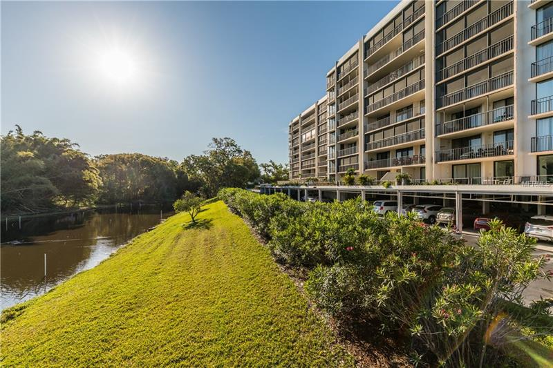 This is a rare chance to own a completely updated corner unit at the Belleair Country Club, which is growing in prestige every day as new amenities and improvement come to completion. This particular unit features a large veranda overlooking a serene pond, from where you can get a glimpse of the Gulf of Mexico. Impact resistant sliding doors lead the visitor from the veranda into a completely remodeled condo featuring large ceramic tiles, new kitchen cabinets, granite countertops and newly done bathrooms. The kitchen and the adjacent dining area flood with morning sunlight, while floor-to-ceiling windows keep the living area bright. A spacious master bedroom includes two large closets and a master bath with floor-to-ceiling tiles and expansive recessed lighting. The second bathroom is equally stunning and sits directly across the hallway from the second bedroom. Enjoy staying home or partake in the large heated pool or fitness center in your building. Your designated parking space is directly under the unit, just a couple of steps away should you chose to use the staircase instead of the elevator. Don't wait, it doesn't get any better than this. Everything has already been done for you in this move-in ready residence so that you can enjoy country club living from day one.