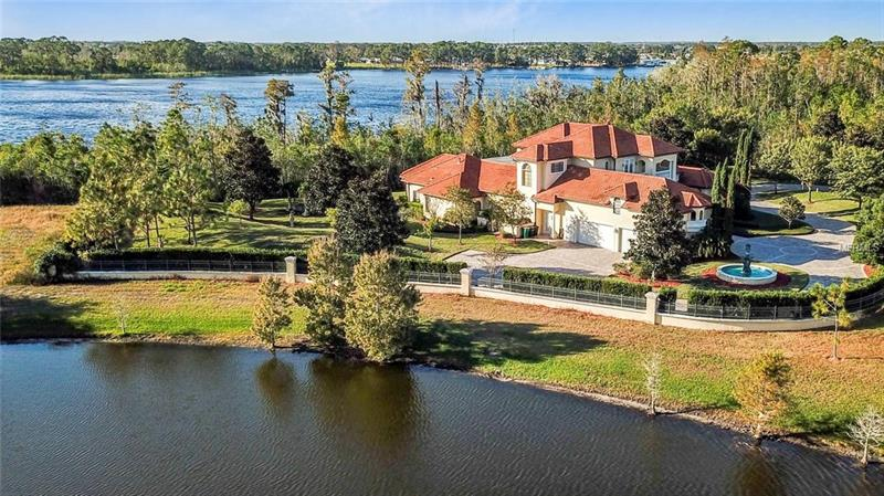 This is THE HOME OF YOUR DREAMS! Enjoy the private luxuries of skiing, boating & living on almost 2 acres of private land nestled on beautiful Lake Davenport. This custom architectural estate home boasts beautiful landscaping, a bright & open floor plan, the finest ARCHITECTURAL DETAILS & finishes, and is a state-of-the-art SMART HOME. Control everything w/ a touch of a finger! The open floor plan boasts a formal living room, family room, & formal dining area. Windows abound allowing the natural beauty of the outdoors to be enjoyed throughout the home. The culinary connoisseur will fall in love with this GOURMET, top of the line, KITCHEN in which the elegant cabinetry, built-in appliances, a large island and granite countertops truly shine. The 1st-floor master suite is a truly serene haven with its tray ceilings, NEW OAK HARDWOOD FLOORING, & a luxurious master bath. Three additional spacious bedrooms w/ private bath await on the second floor. You'll enjoy the additional space your own private THEATER room (with foyer and stadium seating), office/den & separate GYM provide. Rolling hills, manicured park-like grounds, and a meandering brick path await outdoors to welcome you to your PRIVATE UTOPIA. Your detached pool house equipped w/ steam room and sauna are just the icing on the cake to a beautiful pool deck w/ hot tub, cabana bath, summer kitchen & an incredible view. Don't miss your chance to own this beautiful estate home just minutes from coveted Celebration and Disney Springs.