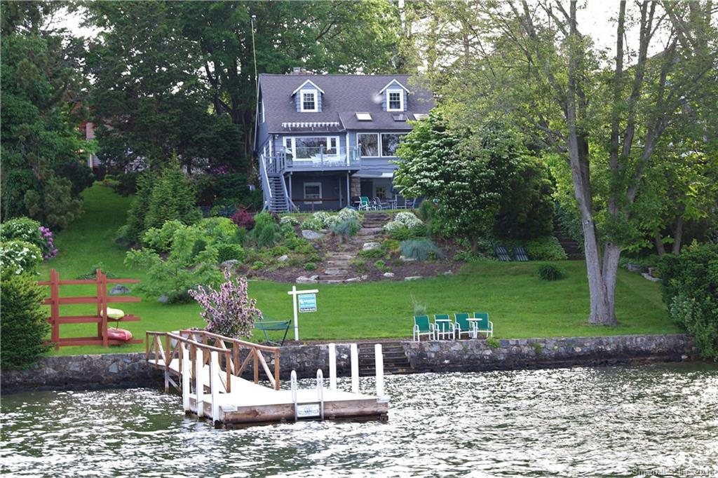 EXPANSIVE LONG LAKE VIEWS  AND LEVEL WATER FRONTAGE IS YOURS in this updated waterfront home with 93' of expansive level lakefront. This waterfront Cape offers all the charm of a lake home with an open floor plan and updated kitchen, baths and 3 fireplaces.  The chef's kitchen has a center island, granite counters and stainless appliances. It opens to the dining room offering walls of windows, skylights, corner fireplace, vaulted ceilings, breathtaking lake views, it also has access to the large deck with glass railings relax and taken in the panoramic lake views.  Entertaining is easy in the living room by the stone fireplace and lake views.  The ML offers a master bedroom with update bath.  The upper level has 3 spacious bedrooms and an updated bath.  The lake level has a cozy den, family room with fireplace, updated lake level bath.  The walk out lake level patio is perfect for a large gathering and offers long lake views.  The gorgeous grounds were professionally landscaped with mature plantings and stone walkways.  The level 93' of water frontage has stone walls and an updated deep water dock. Located in Knollcrest with beach and basketball a short walk away.  There is plenty of storage and a 1 car garage and this home is move in ready to end what lakefront living has to offer.