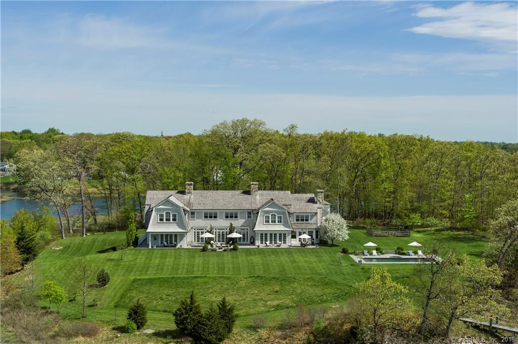 One of the largest waterfront properties in Darien, this magnificent 11-room estate sits on a 7.1 acre private parcel.  The property looks south to Long Island Sound and north to the Goodwives River and Rings End Bridge, with sweeping lawns, gardens and mature trees.  The 8,300 sq. ft. home has a great room with 12' ceilings and two limestone fireplaces, gourmet kitchen w/ breakfast room and family room w/ stone fireplace.  It has 10 sets of french doors to expansive flagstone terrace.  Five en-suite bedrooms w/ water views, eight bathrooms, full walk out basement w/ billiard room, astroturf play room and workshop.  Includes a pool/spa, outdoor shower and dock w/ storage for kayaks/paddleboards.  Property borders 3.2 acre Goodwives Meadow owned by the Darien Land Trust.