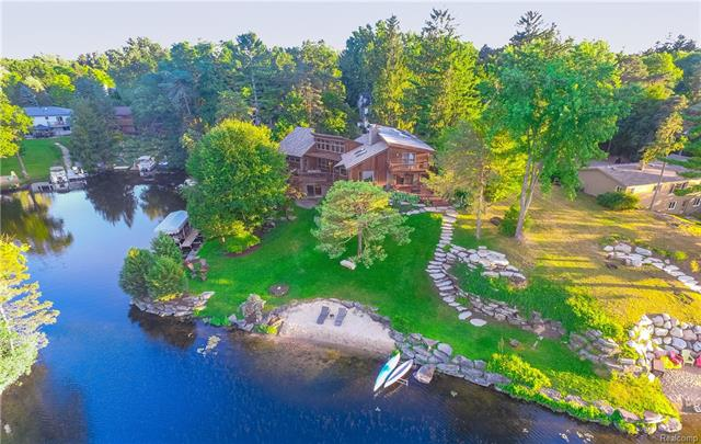 This one of a kind Frank Lloyd Wright inspired design provides 240 ft. of lake frontage nestled on the Point above Indianwood Lake.   A Contemporary & Rustic blend with Soaring Ceilings, Limestone Hardscapes, Rock Sculptures, Gristmill Fountains, Private beach, Boat launch, Kayak Launch, 3 fire-pit areas and a Meditation Platform.  A Serene peaceful spot surrounded by tall pines. This house gets both SUNRISE AND SUNSET!  Stunning views from almost every window. 5 bedrooms 3.5 baths.  Steam shower, Jacuzzi, lower level is an Entertainers dream! Bar & Master Suite walk-out on the lake level. Lots of Windows, Hard Wood, Glass and Stone. A perfect mix of earthy elegance in a relaxed atmosphere.  Red Heartwood tongue and groove built, mahogany doors, copper gutters, reclaimed brick paver driveway from Brick-town in Detroit. 25 Minutes north of Royal Oak but feels a million miles away. Energy efficient HVAC system. Must See to appreciate.