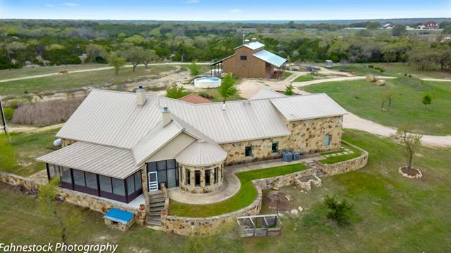 Texas villa on approx.18 acres. Magnificent barn with private study/exercise areas/workshop and shower facilities. Grand views from walls of windows and covered/screened back veranda add additional living area. Upstairs media /game room – lg bedrms with huge master suite. Tanks on property 1500 gal water storage tank/Instant heat on the water heaters/Water run to each pasture/Improved grasses in pasture/Fire suppression system in house/cross fencing/ Recent int. painting.