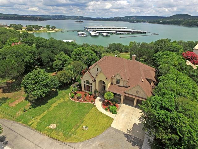 Gorgeous Waterfront Home w/ Spectacular Views of Lake Travis! Hand Scraped Hardwood & Tile Flooring Throughout. Spacious kitchen boasts sizable center island/breakfast bar, arched stone hood, & stainless steel built-in appliances. Family room features soaring ceiling and beautiful picture windows. Master down w/ bay window & large garden tub Outdoor space ideal for entertaining w/ upper & lower decks, separate patio, & expansive backyard offering impressive views and direct access to Lake Travis.