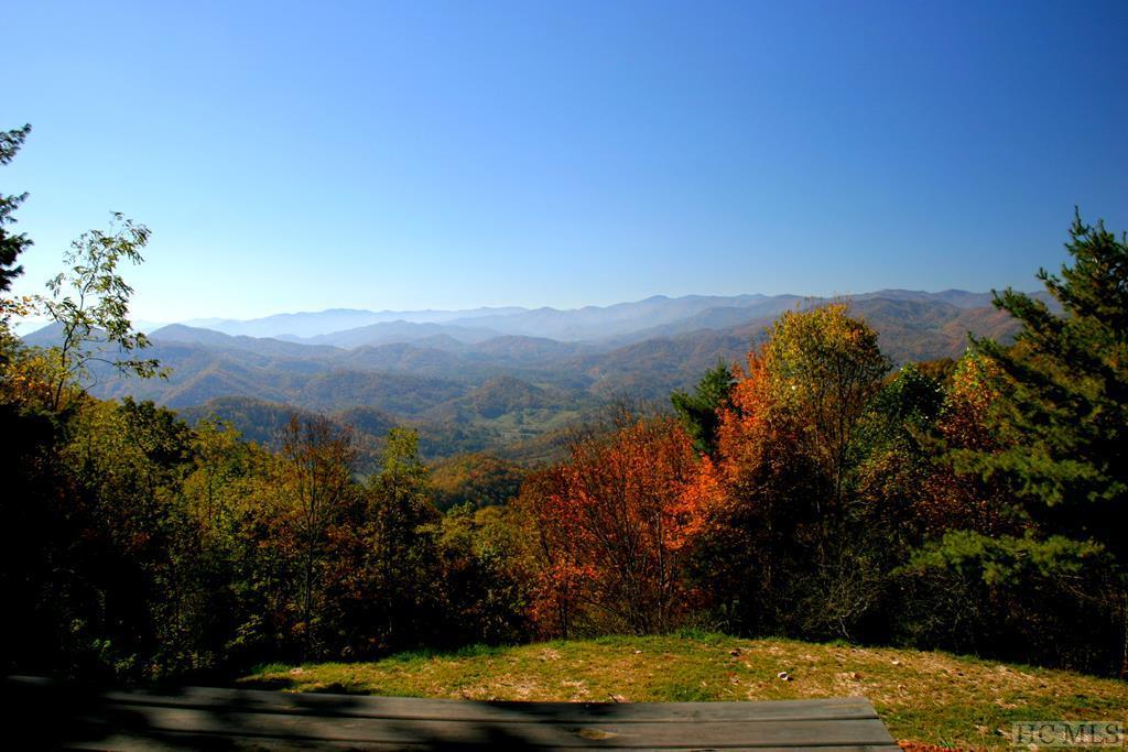 Located in Western North Carolina, 25 mins from Asheville, Milima's 400 acres of pristine land are surrounded by the Smoky Mountains and Pisgah Forest. There is a 8-mile network of trails for hiking and riding that traverse the land ascending from 3200 ft. to 4200 ft. and offer a nature lover's paradise with mountain streams, rare plants and a diverse wildlife population. There is a well built road system and underground power and water on 272 acres running to a selection of estate home sites perfect for future sale should the owner wish to do so. There are separate horse riding trails on the gently contoured terrain of the eastern cove. The property is full of fruit trees and acorn-bearing trees, indigenous to the mountains and essential to the welfare of wildlife and mountain songbirds. Forest openings benefit ruffed grouse, wild turkeys, deer, elk and songbirds, to name a few. Milima Ranch is a destination of 4 seasons. The winter offers some exceptional snow days with the landscape transforming into a dramatic canvas that reveals the backbone of the land which is hidden in the growing season. The spring, summer and fall months present an ever-changing canvas of the mountains and the wildflowers are a sight to be seen. September brings the ripening of the apple trees that are scattered throughout the 400 acres, followed shortly after by the fiery fall leaf season. Moonshine cabin is a lovely 3br/3.5ba log home nestles perfectly in a cove by the creek and looks out over the valley towards ranges of beautiful mountains.  It features much charm and many luxuries, from the gourmet kitchen, to the sleeping porch overlooking a mountain stream. The great room, features old barn wood, hewn wood beams and poplar bark. There are also several outbuildings including a barn, equipment storage building and camping platforms overlooking the most peaceful views. Another cabin located on the property is also available for purchase separately. This property is truly breathtaking!