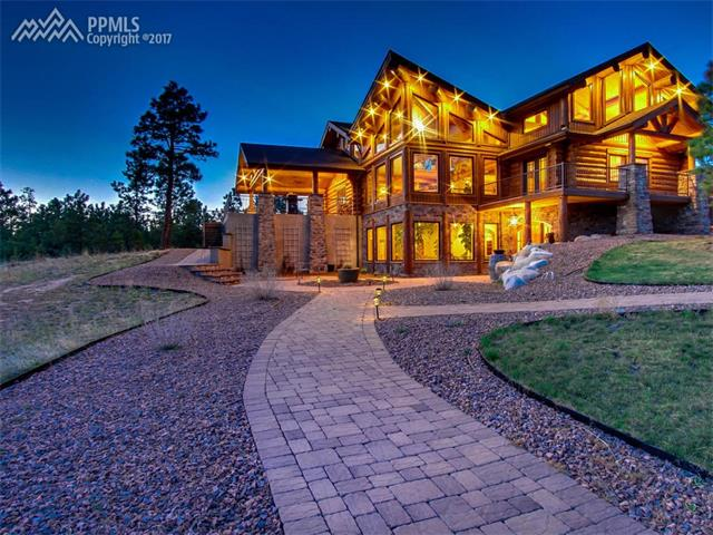 Spacious & Elegant Log Design on 10+ Acres*Privacy galore & Horses OK*Enter into the Slate Foyer featuring a jaw dropping Atrium soaring Upward 3 Floors surrounded by a Wall of Windows showcasing Outdoor Living Space & Massive Pike Peak Views*Great Room concept w/ extensive log accents & impeccable ceiling detail a plus*Focal, full stone Wood Burning Fplce. Rich Walnut Hardwood Floors, stunning master suite, impressive lofted living w/ massive views*Gourmet kitchen w/ Knotty Alder cabinets, granite tops, brkfst bar, WOW!\nPeer thru the Atrium Below and enjoy the bubbling rock water feature*Peaceful Meadow, Forests, & YES, incredible views of Pikes Peak. Set Up Your Delicious Buffet in the Gourmet Kitchen with Top of the Line Appliances, Gleaming Granite Counters, Knotty Alder Cabinetry & Custom Copper Sink. The Dining Room Makes Every Dinner Party Special, but for More Casual Occasions, the Dining Area off the Kitchen is the Perfect Spot, or Open the Double Doors and Walk Out to Expanded Slate Covered Deck, Large Enough for Several Tables of Guests. A Cozy Bar/Pub with Built-In Bar, is a Great Place for After-Dinner Conversation & Enjoying the Evening of City Lights or Watching Your Favorite Movie. Enjoy More Entertaining Space in the Lower Walk-Out Level, with a Theater Room, Surround Sound & Adjoining step behind Kitchen/Wet Bar. This Very Special Home Features 2 Lower-Level Bedroom Suites w/ Bathroom and Plenty of Privacy for Visiting Guests. When it's Time to Relax, Retreat to the Master Suite with Open Beam Log Ceiling, Large Walk-in Closet and Luxurious Master Bath with a Walk-through Shower and Tile Flooring Throughout. More Incredible Views & a Great Retreat in the Light-Filled Loft Area (4th bedroom possible w/ conversion in the loft area) * One of a kind, Loaded!