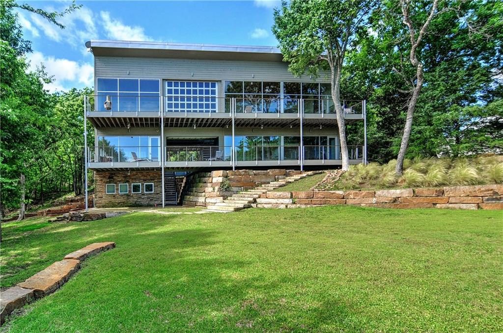 THIS 4 BR 5 BA HOME HAS LAKE ACCESS, ONE BOAT SLIP, AND IS LAKE FRONT WITH A SPECTACULAR WATER VIEW! THE HOME FEATURES EXPANSIVE WINDOWS AND ROLL-UP DOORS, BRINGING THE OUTSIDE IN. GREAT MODERN DESIGN & LAYOUT WITH LIVING UP & ROOMS DOWN AFFORDS PRIVACY FOR LARGE FAMILIES, MAKES PERFECT USE OF AVAILABLE SPACE. SUPERB OPEN KITCHEN! LARGE DECK FOR ENTERTAINING WITH A VIEW. GORGEOUS LANDSCAPED LAWN WITH FIRE PIT AND PLENTY OF SHADE FOR RELAXING.
