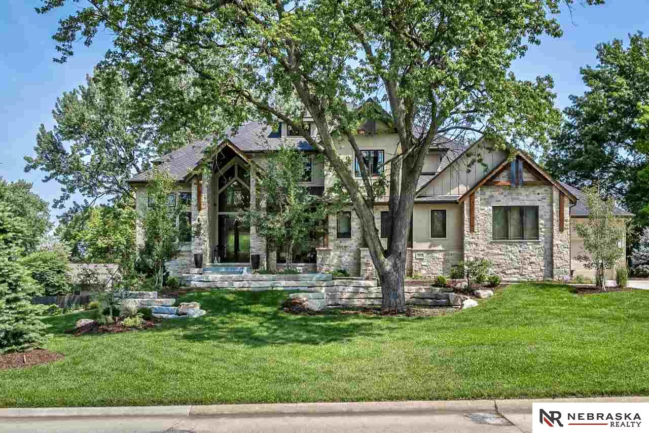 Exquisite, yet comfortable! This custom built 2 story home offers a gourmet kitchen w/ seldom seen brushed granite counter tops, oversized island, GE Monogram appliances & a 6 burner gas range w/ grill. Oversized drop zone w/ 2nd laundry rm right off the massive 4 car garage w/ built-in storage. Custom French doors lead you into sunroom w/ another stone fireplace. LL features exercise rm w/ commercial grade flooring, bar area w/ beautiful granite & 2 bedrooms. So much more to list here.