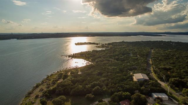 Nestled between an empty lot & Windy Point Park, this 5.8 acre w/ 227 ft of waterfront on main basin of Lake Travis faces SW towards Mansfield Dam. There is a 10,000+/- sf 2-story metal structure w/living quarters & garages next to the street. There is also a 1,200+/- sq ft cabin midway to the water which is grandfathered. Property is fenced, gated & heavily treed w/a volleyball court & concrete boat ramp allowing recreational water access. This would make for a great Corporate Retreat or Family Compound!