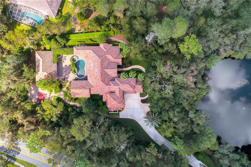 """This 6700+ sqft secluded, completely custom home sits on nearly two acres of meticulously landscaped paradise, centrally located in Heathrow's premier golf community with 24/7 guarded access.  A truly one-of-a-kind, fully custom property, this palatial compound boasts 8 bedrooms, 6 baths, a pool and a detached mother-in-law suite. This home is a MUST-SEE.  As you pull into the private, extensive driveway on your way to the over-sized, side-entry three (3) car garage complete with copious storage, you will be welcomed home by breathtaking scenic views. You'll step into formal dining and living areas adorned with authentic oak. Your 42"""" hand-crafted wood kitchen cabinetry coupled with stainless steel appliances and custom granite countertops will make you the toast of the neighborhood.  Step through the pocket sliding doors and relax alongside the most breathtaking pool/spa and summer kitchen you'll ever see, including a stone waterfall and Jacuzzi. Your guests will fight to enjoy your lighted basketball court and chipping green.  Every room features a stunning view without compromising privacy, while a whole-house generator guarantees that you'll continue to live in luxury, even in the harshest of weather.  Welcome home!"""