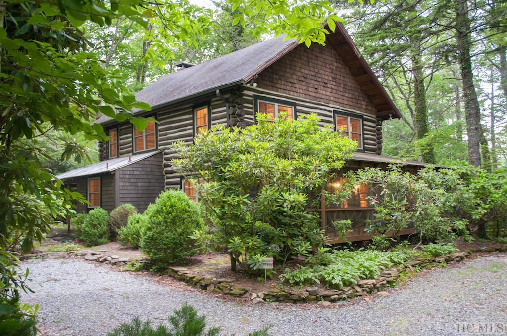 This pristine Historical Joe Webb log cabin has been renovated from top to bottom! New tile and luxurious baths, designer kitchen with new upgraded appliances, custom cabinets, gorgeous granite, gleaming hardwood floors, beautiful screened porch, courtyard dining area with fireplace...everything has been done for you. A winding path leads to a stream-side gazebo for napping or reading with your favorite vino in hand. The home is nicely sited on a level lot with natural beauty and rhododendrons with very low maintenance. A side and front porch for dining are great for entertaining. Located in a prime location just 5 minutes to downtown Highlands!  Come enjoy the serenity this home has to offer!