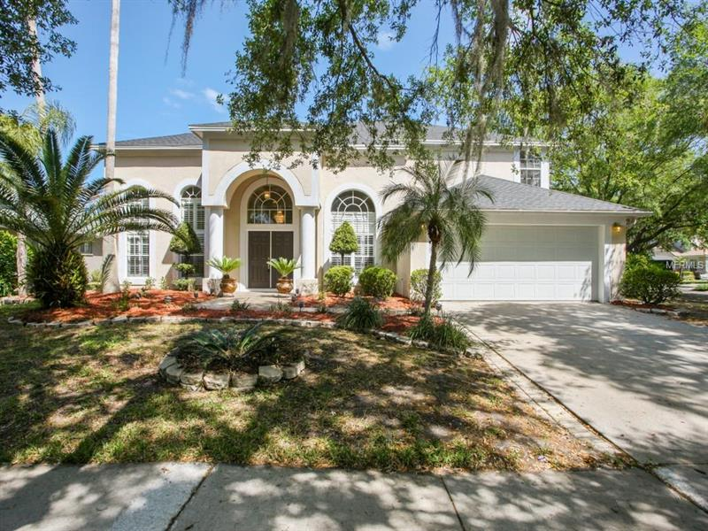 """Gorgeous 2-story pool home on a corner lot in the highly desired community of Manchester Village in Tampa Palms! 2,577 square feet of living space w/ 4 bedrooms, 3 1/2 baths, 2-car garage, mature trees & tropical landscaping. As you enter through the double doors into the foyer, lovely pool and backyard views can be seen. This home features both a formal living & dining room, plus many architectural upgrades like tray ceilings, columns, decorative niches, plantation shutters & plenty of large windows for natural light. The recently remodeled kitchen is a chef's dream, boasting 42"""" solid cherry wood with toffee glaze cabinets, gleaming granite counters, center island, breakfast bar, stylish backsplash, pantry, new appliances & gas stove. Enjoy casual dining in your nook w/ views of the lanai thru triple windows, plus a gorgeous built-in desk/storage unit. Cozy up to the fireplace in your family room, which is adjacent to the kitchen & opens to the covered & screened lanai & pool, making it ideal for entertaining! The huge master suite enjoys crown molding, dual sink vanities with granite, upgraded faucets & mirrors, plus relaxing garden tub & walk-in shower. Mounted TVs in Master bedroom and on lanai.  This home is just minutes to I-75, Moffitt, USF, University Community Hospital, Florida Hospital, shopping malls, popular restaurants & top rated schools. Walking distance to Chiles Elementary, Hampton Park & Club Tampa Palms. Welcome Home!"""