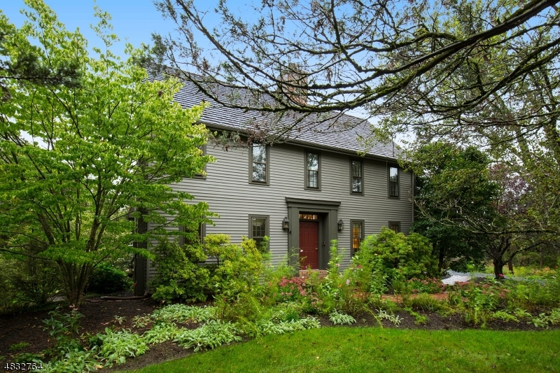 Nantucket Meets Refined Country, Rich Period Reproduction Colonial, Tewksbury Township             A private, premier Tewksbury location on two landscaped acres creates a bucolic setting for quality life and time, in this custom-built country period Colonial, in Tewksbury Township. The flowing floor plan measures over 3,200 square-feet and offers four bedrooms, two full baths and a powder room, plus an attached two-car garage.  Enhanced by its private setting backing to woodlands, the park-like backyard offers English gardens, authentic brick walkways and an entertainment-friendly deck overlooking tranquil views. Finished in cedar siding and capped by a cedar shake roof, this classic 1985-built home replicates the look of vintage architecture while incorporating a variety of graceful new updates. Interior highlights include lustrous hardwood floors, neutral paint colors, two fireplaces and Jotul™ wood stove, classic millwork, beamed ceilings, French doors, a newer chef's kitchen, a 2018 master bath renovation and upgrades in secondary baths.          A landscaped brick walkway leading to the transom-topped front door opens to a welcoming foyer flanked by formal living and dining rooms. The elegant living room is anchored by a white-mantled brick fireplace and has a set of French doors opening to the enclosed sun porch. Lined in traditional moldings, the formal dining room easily hosts special occasions and adjoins a well-equipped butler's pantry. An updated chef's kitchen set under beamed ceilings presents granite countertops, richly-toned wood cabinetry, a tumbled marble backsplash and full complement of stainless steel appliances. The kitchen's hardwood floors extend into a sunny dining area with bow window. This part of the home opens directly into the family room anchored by a brick wall fireplace and graced with beamed ceilings, knotty wood paneling, Berber carpeting and a staircase to the finished lower level.   The serene upstairs master suite offers a luxurious spa-like master bath updated in 2018 with an oversized clear frameless glass shower, pedestal sink and ceramic tilework. Three additional, spacious bedrooms share another full bath on this level featuring 2015 updates of a subway tile-framed soaking tub/shower, customized open wood vanity with poured concrete counter, bead board walls and mosaic tile flooring. Additional living space in the partially finished lower level offers a recreation room with knotty wood paneling, a brick wall featuring a Jotul™ wood stove, and home office with bookcases.   This home's premier Tewksbury Township location is near charming village shops and restaurants in the historic village of Oldwick.  Transportation and a network of local and interstate highways are available locally for access to New York City and Newark Liberty International Airport.  The entire area has a notable history dating back to the pre-Revolutionary War era, and retains much of its original character. Fine old homes, equestrian estates and working farms dot the open landscape of rolling hills and fields.