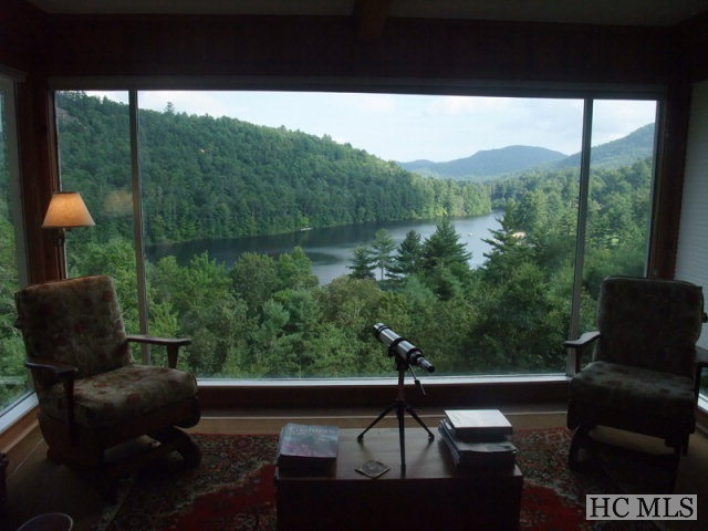 The Round Hill home features FAIRFIELD LAKE FRONTAGE  (approximately 229 feet) and one of the MOST SPECTACULAR VIEWS OF FAIRFIELD LAKE and the surrounding mountain ranges with your TWO-ACRE setting ...and comes totally and very nicely furnished!  Definitely one of the BEST VIEWS IN THE VALLEY WITH THE COMBINATION OF LAKE AND MOUNTAINS!   Golf cart (included) access to the Country Club of Sapphire via path on other side of 64. VERY FEW HOMES EXIST in Round Hill with Fairfield Lake frontage, currently only ten homes/lot besides for Camp Merrie-Woode property.  Enter the Great Room with huge picture window that looks at the views, along with lots of wood for mountain charm. Main level all hardwood floors. Great Room with stone fireplace and a couple living arrangements, along with dining area. Huge covered upper deck to enhance your outdoor entertaining areas to enjoy your views!  Kitchen has eating area along with granite countertops.  Home has path to lake that takes you to your private dock, swing and picnic bench on the lake (Camp-Merrie-Woode entrance), or drive around to the lower road with easier access to your dock.  Master suite with the views and private bath and one-half on main floor. Guest bedroom with private bath also on main floor. Powder room located off living area.  Lower level with three bonus rooms to be used as office/kitchenette, hobby room, den, along with full bath. Another huge covered deck on lower level also. Sapphire Valley amenities ($776-2018) available, but optional. Ask about septic update information. This location is the best ... enjoy Fairfield Lake fishing, canoeing, swimming, walk the lake trail, small sailboats. Non-motorboat lake, only trolling motors allowed.