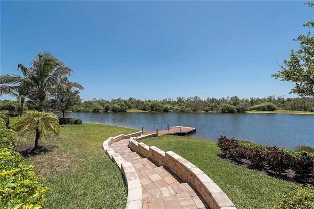 Breathtaking wide water creek views can be seen from nearly every room and this home features a private dock — rarely available in Fiddler's Creek! Relax on the extended brick paver lanai featuring a full summer kitchen with refrigerator, a saltwater pool, infinity spa, decorative spillover water bowls, covered & sun-exposed seating areas, and solid stucco framed mansard screen. This home is beautifully landscaped with lighting front and back. The interior is decorated with staggered chiseled edge tile throughout, plantation shutters, dramatic coffered ceilings with speakers, and upgraded fans and fixtures. The open kitchen is appointed with antique white cabinetry, tile backsplash, granite countertops, and stainless steel GE Monogram appliances including a gas cooktop. Dine in the breakfast room or formal dining room. The spacious master suite features an en suite with dual vanities, frameless walk-in shower with 2 heads and soaking tub. Offered furnished. Additional features include a laundry room with newer GE Profile appliances, smart home technology, extra GE refrigerator, and a Kinetico water filter/softener. Brand new sleep number bed included.